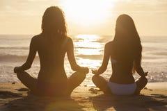 Muchachas de las mujeres que sientan la playa del bikini de la puesta del sol de la salida del sol Foto de archivo libre de regalías