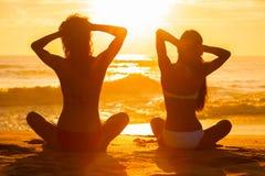 Muchachas de las mujeres que sientan la playa del bikini de la puesta del sol de la salida del sol fotografía de archivo
