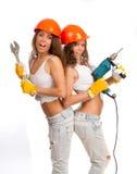 Muchachas de los géminis en cascos anaranjados Foto de archivo libre de regalías
