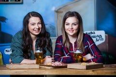 Muchachas de partido Muchachas hermosas que beben la cerveza en barra Amigos de muchachas que tuestan y que comen en el pub Fotografía de archivo libre de regalías