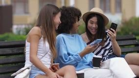 Muchachas de risa que miran el vídeo divertido en línea en el teléfono almacen de video