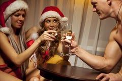 Muchachas de Santa que tintinean los vidrios de champán con el hombre Fotografía de archivo