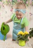 Muchachas de tres años de cuidado para las flores, Fotografía de archivo