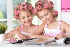 Muchachas de Tweenie en bigudíes de pelo con la revista Fotos de archivo libres de regalías