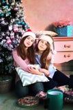 Muchachas del adolescente con el árbol de navidad y los presentes Imagen de archivo