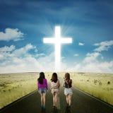 Muchachas del adolescente en el camino con una cruz Fotos de archivo