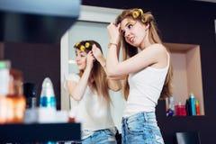 Muchachas del adolescente que aplican los rodillos del pelo en su pelo rubio largo que se prepara para salir Fotografía de archivo libre de regalías