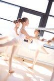 Muchachas del ballet en la elevación reversa de la pierna que sostiene una barra Fotografía de archivo libre de regalías
