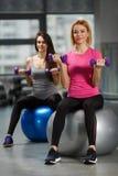 Muchachas del deporte en gimnasio que ejercitan con pesas de gimnasia Imágenes de archivo libres de regalías