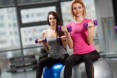 Muchachas del deporte en gimnasio que ejercitan con pesas de gimnasia Fotos de archivo