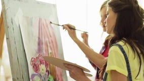 Muchachas del estudiante con la pintura del caballete en la escuela de arte almacen de video