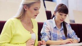 Muchachas del estudiante con los cuadernos en sala de conferencias almacen de video