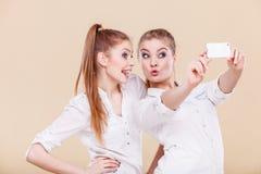 Muchachas del estudiante de los amigos que toman la foto del uno mismo con el teléfono elegante Imagenes de archivo