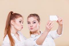 Muchachas del estudiante de los amigos que toman la foto del uno mismo con el teléfono elegante Fotografía de archivo