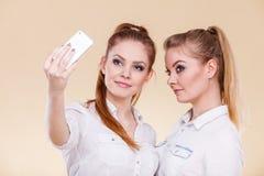 Muchachas del estudiante de los amigos que toman la foto del uno mismo con el teléfono elegante Fotos de archivo libres de regalías