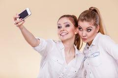 Muchachas del estudiante de los amigos que toman la foto del uno mismo con el teléfono elegante Imagen de archivo libre de regalías