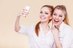 Muchachas del estudiante de los amigos que toman la foto del uno mismo con el teléfono elegante Fotografía de archivo libre de regalías