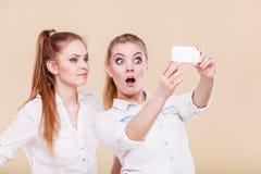 Muchachas del estudiante de los amigos que toman la foto del uno mismo con el teléfono elegante Imagen de archivo