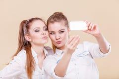 Muchachas del estudiante de los amigos que toman la foto del uno mismo con el teléfono elegante Imágenes de archivo libres de regalías