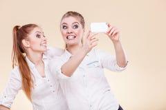 Muchachas del estudiante de los amigos que toman la foto del uno mismo con el teléfono elegante Foto de archivo