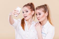 Muchachas del estudiante de los amigos que toman la foto del uno mismo con el teléfono elegante Fotos de archivo