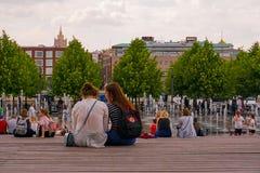 Muchachas del estudiante que se sientan en el banco, descansando en el parque, primavera en Moscú imagen de archivo