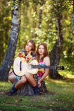 Muchachas del Hippie con la guitarra al aire libre Imagen de archivo