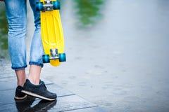 Muchachas del inconformista con el monopatín al aire libre en la lluvia Skatebord del primer en mano femenina Mujer deportiva act Fotografía de archivo libre de regalías
