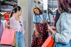 Muchachas del inconformista que eligen la ropa en el boutique, concepto de las muchachas de compras de la moda Foto de archivo libre de regalías
