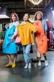 Muchachas del inconformista que eligen la ropa en el boutique, concepto de las muchachas de compras de la moda Foto de archivo