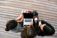muchachas del inconformista que miran algo en el red-libro portátil con la pantalla en blanco del espacio de la copia para el men Imágenes de archivo libres de regalías