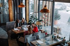 Muchachas del inconformista que se sientan en cafetería y detalles de organización de la cooperación Foto de archivo