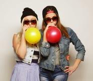 Muchachas del inconformista que sonríen y que sostienen los globos coloreados Foto de archivo libre de regalías