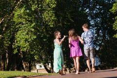 Muchachas del muchacho que caminan risa lejos que habla Imagen de archivo libre de regalías