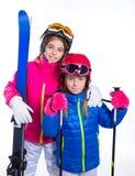 Muchachas del niño de Siters con las gafas del casco y de la nieve de los polos de esquí Fotos de archivo