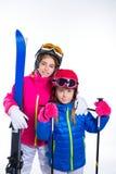 Muchachas del niño de Siters con las gafas del casco y de la nieve de los polos de esquí Fotografía de archivo libre de regalías