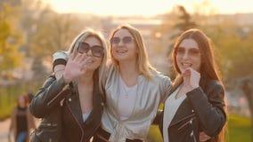 Muchachas del paseo de la tarde de la diversión de las señoras jovenes que invitan para unirse a metrajes