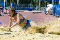 Muchachas del salto de longitud con la arena del espray Imagen de archivo libre de regalías