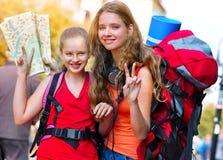Muchachas del viajero con la mochila que busca el mapa de papel turístico de la manera foto de archivo
