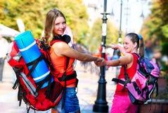Muchachas del viajero con la mochila wallking en ciudad cultural europea foto de archivo