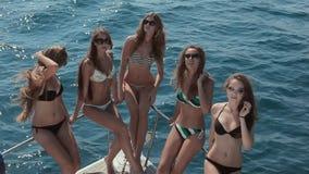 Muchachas delgadas en el bikini que se sienta en la popa de