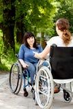Muchachas discapacitadas en las sillas de ruedas durante hablar imagen de archivo