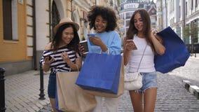 Muchachas diversas del comprador que comparten el contenido con los teléfonos almacen de video