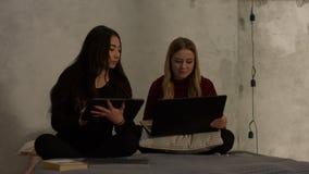 Muchachas diversas que estudian con los dispositivos electrónicos metrajes