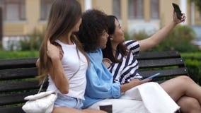 Muchachas diversas relajadas que hacen el selfie en el banco almacen de video