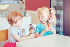 Muchachas divertidas de los ni?os que se sientan junto compartiendo el helado imágenes de archivo libres de regalías