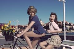 Muchachas divertidas del vintage en la bicicleta cerca del mar Imágenes de archivo libres de regalías