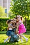Muchachas divertidas que caminan en el c?sped con su madre Las hermanas juegan as? como mam? Cuidado maternal Familia feliz imágenes de archivo libres de regalías
