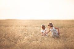 Muchachas divertidas que juegan con centeno en la puesta del sol, forma de vida imagen de archivo libre de regalías