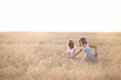 Muchachas divertidas que juegan con centeno en la puesta del sol, forma de vida fotografía de archivo